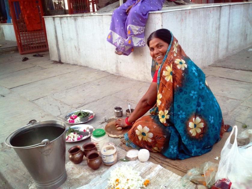 कोटेश्वर महादेव पर फूल-माला-पूजा सामग्री देने वाली महिला।