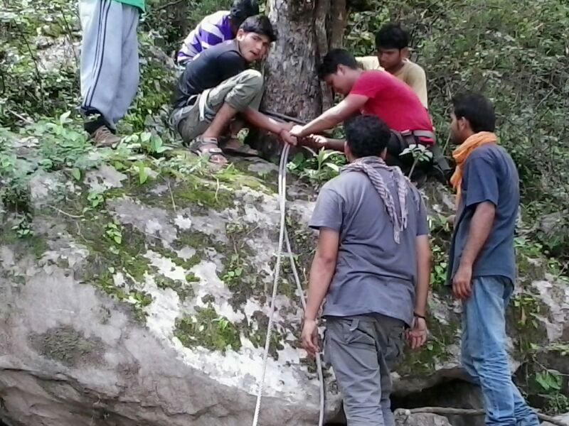 लोग एक पेड़ से तार बांध रहे हैं रोप वे बनाने के लिये