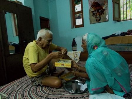 मेरी बुआ मेरे पिताजी को सिर पर जरई रख कर मिठाई खिलाती हुई।